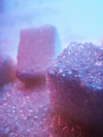 Heap of transparent white sugar crystals with large pieces of sugar in mixed colour light. Macro photo
