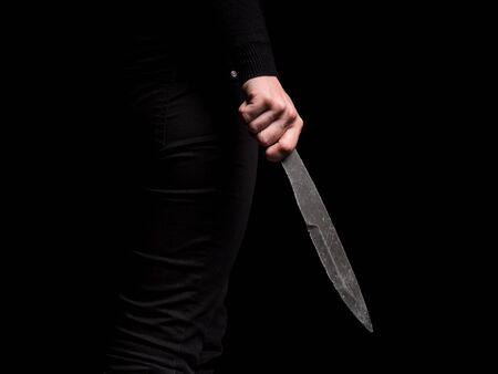 Girl holding in hand steel throwing knife on black background Stockfoto