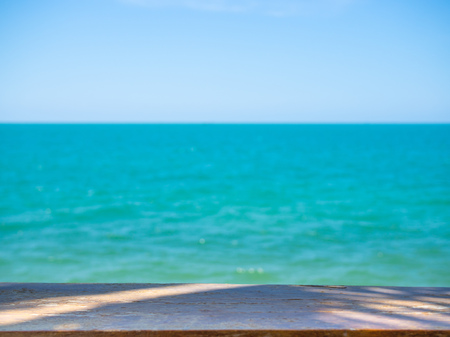 Empty Top of Wooden Table with Shadow of Coconut Palm Tree Leaves on Blurred Seaview and Blue Sky Summer Background