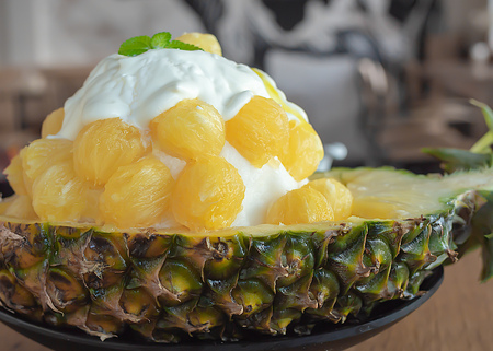Ice Cream Snow Flake. Sweet Dessert Korean Style call Bingsu with Pineapple Flavor Ice Ball in A Bowl Made by A Half of Fresh Pineapple on Wooden Table Cafe Background