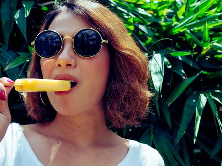 Mooie vrouw kort haar dragen wit overhemd en ronde zonnebril eten gele Popsicle Ice Pop smelten op zomertijd met zon op boom achtergrond