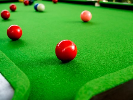 Red and Colorful Snooker Balls Near Corner Hole on Green Snooker Table Stock Photo