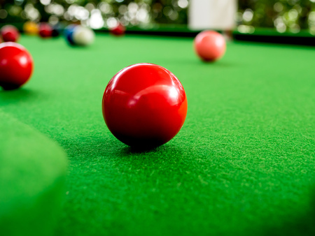 Red and Colorful Snooker Balls Near Corner Hole on Green Snooker Table 免版税图像