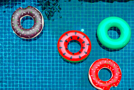 Colorful Pool Float Rings are Floating on Swimming Pool Background, Summer Concept