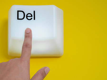 Finger is Pressing Big Delete Computer Key Button Light Box Isolated on Yellow Background with Space. Eraser Concept.