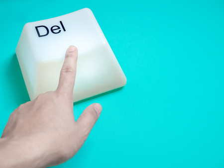 Finger is Pressing Big Delete Computer Key Button Light Box Isolated on Aqua Blue or Green Background with Space. Eraser Concept. Standard-Bild