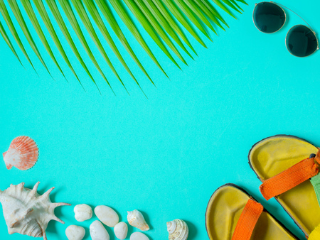 Flat Lay Traveler Accessories, Colourful Sandal, Sunglasses with Beach Seashells, Beach Pebbles and Coconut Palm Leaf on Aqua Blue Background with Blank Text Space. Top View Vacation Summer Concept.