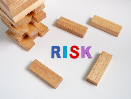 Risk Colorful Text with Tumble Tower Wooden Block Game on White Background. Business Concept