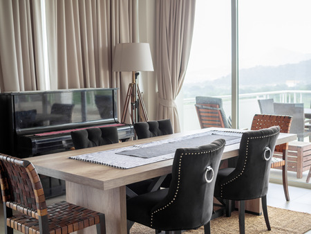 Modern Luxury Dining Room Interior with Wooden Dining Table, Luxury Chairs on The Carpet, Classic Piano, Floor Lamp and The Curtain Near The Terrace Outside with Mountain View.