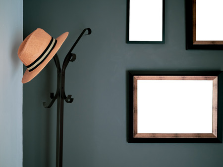 Orange Fashion Hat Hanging on Black Vintage Standing Hat and Coat Hanger with Blank Frames on The Dark Green Wall.