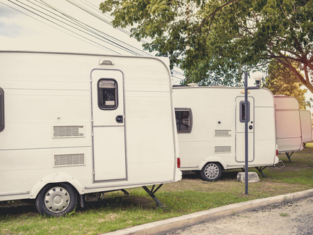 White caravan camping trailer cars, motorhomes parking in the garden. Stock Photo - 105010771
