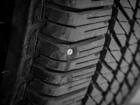Close-up of rubber tires leak, The metal nail puncturing the tire