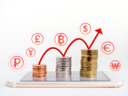 Making money online. Business financial online concept. money, stack of colourful coins on mobile phone with red rising up arrow graph on coins and currency icons on white background with copy space.