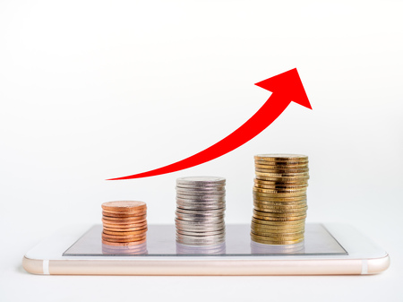 Making money online. Business financial online concept. money, stack of copper, silver and gold Coins on mobile Phone with red rising up arrow graph on coins isolated on white background with copy space.