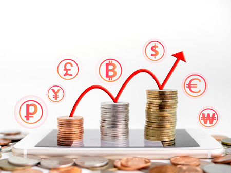 Making money online. Business financial online concept. money, stack of copper, silver and gold coins on mobile phone with red rising up arrow graph on coins and currency icons isolated on white background with copy space.
