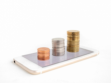 Making money online. Business financial online concept. money, stack of copper, silver and gold coins on mobile Phone isolated on white background with copy space.