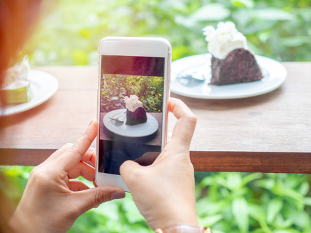 Hands shooting chocolate cake on white plate on wooden table from a smart phone camera on green garden background in cafe. Stock Photo