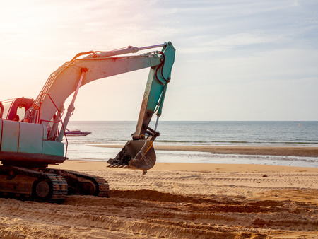 Blue or green Excavator working on the beach with sea view on sunset. Excavator Tire track on sand with sunlight in the evening on seascape background.