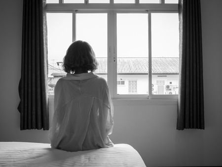 Woman short hair sitting on the white bed in hotel room . Lonely woman looking out the window alone in white hotel room, black and white style.