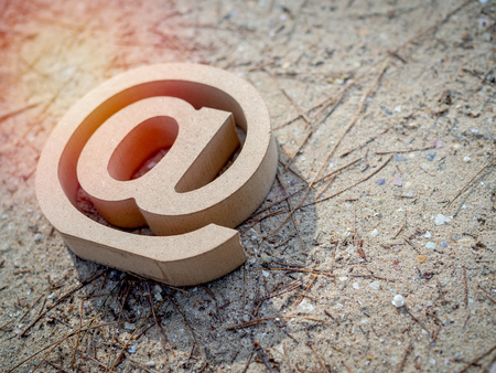 Wooden E-mail address symbol, arroba icon on sand beach texture background with sunlight with copy space. E-mail marketing online internet, technology and environment concept.