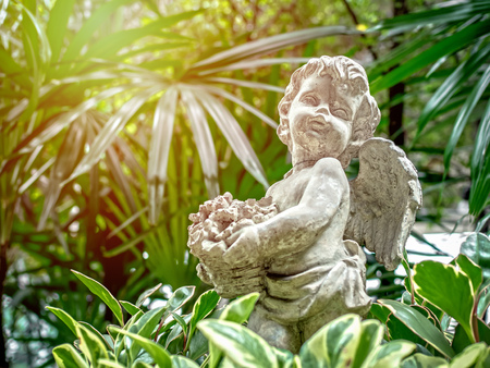 Old little vintage cupid statue holding the flowers in basket on green nature background with sunlight. Banque d'images