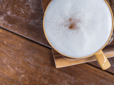 Close-up white foam cover on top of a cup of hot coffee on wooden tray on wooden table background top view with copy space. Reklamní fotografie