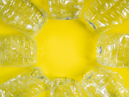 Empty crushed recycle clear plastic drink water bottles on yellow background with copy space. Global warming concept.