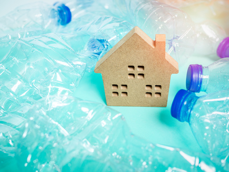Wooden house and empty crushed recycle clear plastic drink water bottles on blue background with light and copy space. Global warming concept.