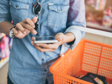 Woman wearing blue jeans shirt and sunglasses using mobile phone to compare price and holding orange shopping basket in mini mart background. Standard-Bild - 108823558