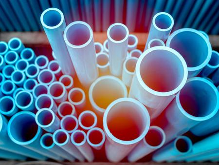Tubos de PVC apilados en almacén. Fondo de tubos de PVC azul con luz solar.