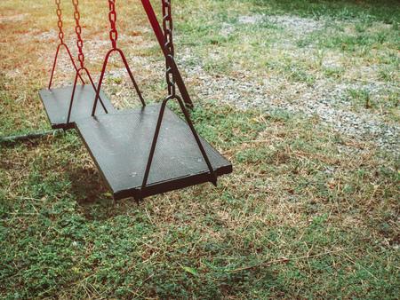 Alte Holzkettenschaukel auf dem grünen Gras im Spielplatz mit Kopierraum.