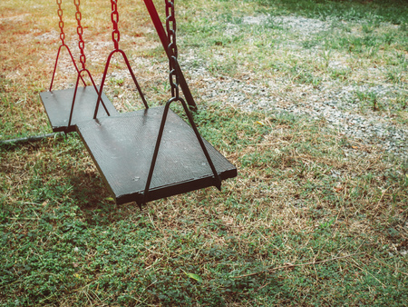 Old wooden chain swing on the green grass in playground with copy space.