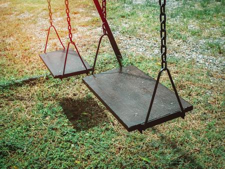 Old wooden chain swing on the green grass in playground. Standard-Bild - 111019730