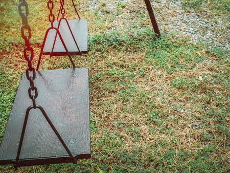 Old wooden chain swing on the green grass in playground with copy space. Standard-Bild - 111019731
