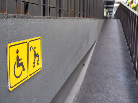 Wheelchair and stroller yellow sign and on the wall and ramp on building background.