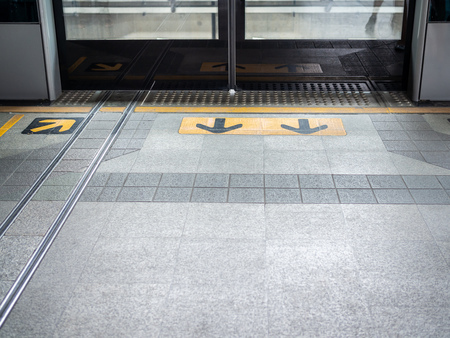 Waiting area on skytrain station. Yellow arrow sign pointing and safety line to the entrance and exit of the door on the floor with copy space.
