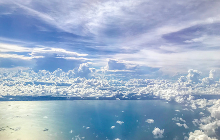 Cloudscape. Beautiful clouds, sky and sea, aerial view from airplane window. Blue sky above the clouds with the ocean. 免版税图像