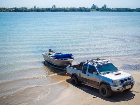 Barco de motor tirado con el remolque de la camioneta en la playa.
