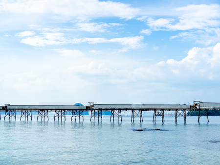 Industrial jetty for loading facility in the sea on blue sky background with copy space.