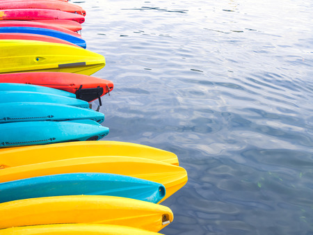 Row of colorful fiberglass kayaks in the sea with copy space.