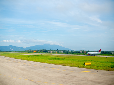 Airplane on the runway with green field and blue sky and mountain background.