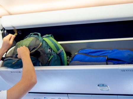 Passenger hand putting green backpack on locker number 10 in the economy class cabin in low cost airline airplane.