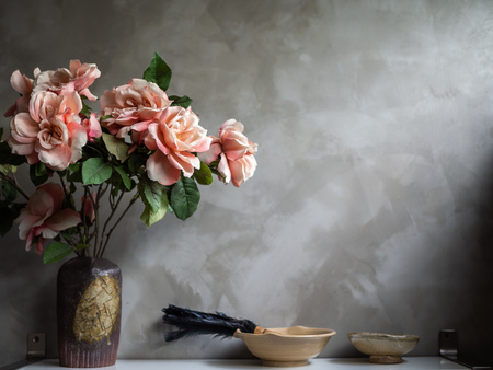 Beautiful artificial vintage pink roses flowers in vintage ceramic vase and pottery on shelf on concrete wall background with copy space.