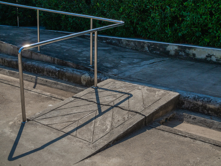 Old grunge wheelchair ramp with metal bar on green bush background.