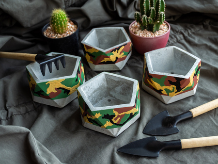 Modern geometric pentagon concrete planters with camouflage pattern painting with cactus plants and garden tools set on green military fabric. Painted concrete pots for home decorations. 版權商用圖片