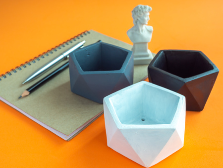 Modern geometric pentagon concrete planters with notebook, pen, pencil and small David statue on orange background. Painted concrete pots for home decoration minimalist style. 版權商用圖片