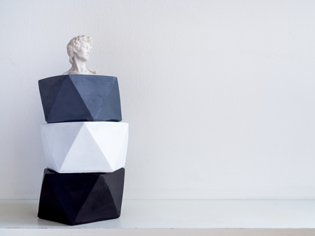 Stack of modern geometric pentagon concrete planters with small David statue on white shelf and white wall background with copy space. Painted concrete pots for home decoration minimalist style.