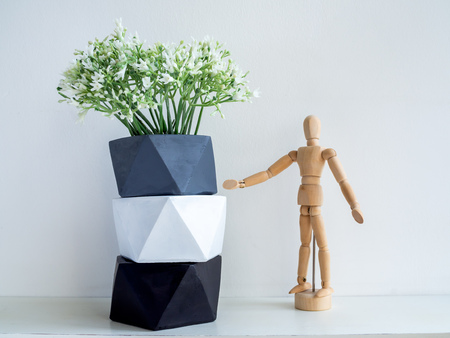 Stack of modern geometric pentagon concrete planters with white flowers and wooden figure on white shelf and white wall background. Painted concrete pots for home decoration minimalist style.