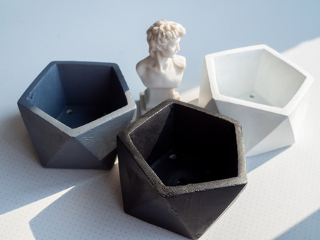 Modern geometric pentagon concrete planters with small David statue on white background. Painted concrete pots for home decoration minimalist style.