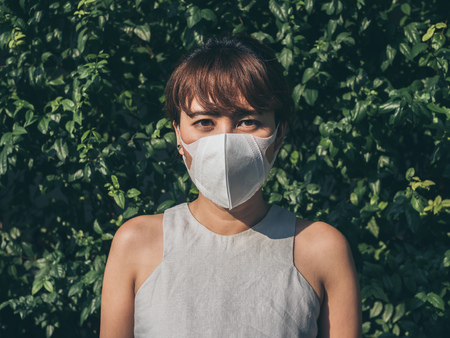 Beautiful asian woman wearing white protective N95 dust mask on green leaves background. Protection against pollution concept.